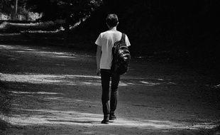 Un jeune homme seul sur une route
