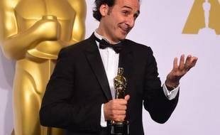 """Alexandre Desplat avec son Oscar de la meilleure bande originale pour """"The Grand Budapest Hotel"""" le 22 février 2015 à Hollywood"""