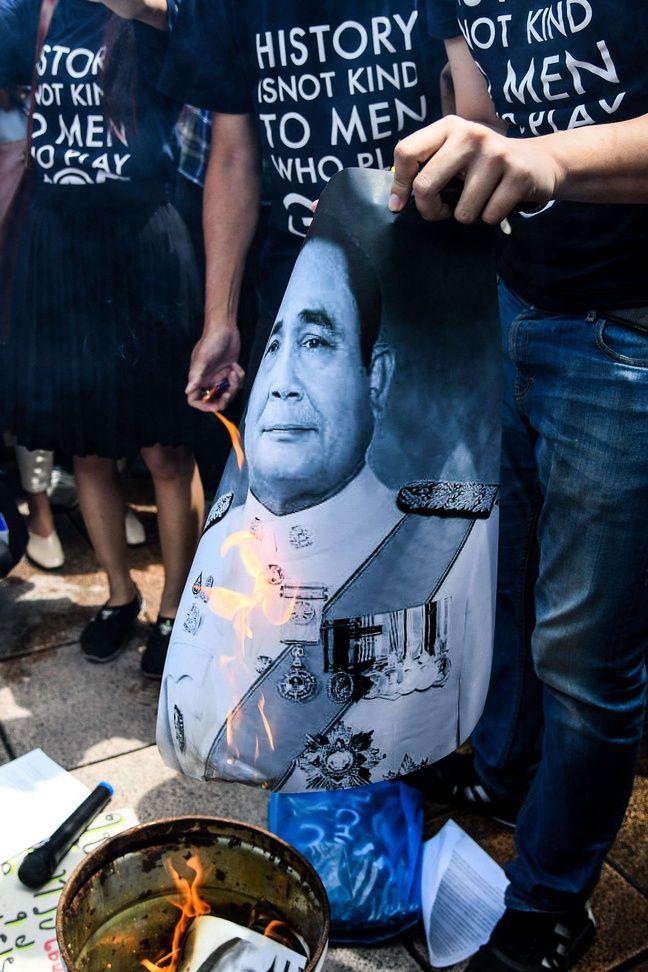 Des étudiants brûlent le portrait du Premier ministre Prayut Chan-o-cha devant le siège du gouvernement lors des manifestations à Bangkok le 24 juillet 2020.