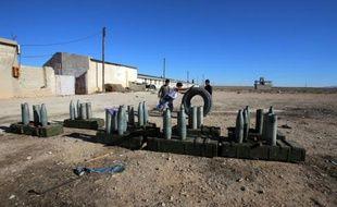 Des enfants syriens jouent avec un pneu près d'un canon  à Sadad le 14 novembre 2015