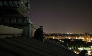 Un toiturophile admire Paris en silence.