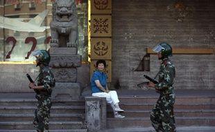Une femme regarde passer des soldats de l'armée chinoise dans une rue de Urumqi, le 9 juillet 2009.