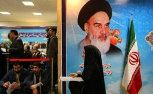 Sous une photo de l'ayatollah Khomeiny, des Iraniens attendent au ministère de l'Intérieur, le 21 décembre 2015 à Téhéran, pour enregistrer leur candidature aux élections législatives et de l'Assemblée des experts prévues le 26 février 2016