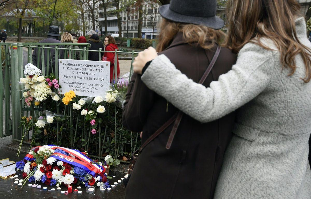 Le 13 novembre 2016, deux jeunes femmes se recueillent devant la plaque commémorative apposée rue de la Fontaine au Roi, près du café la Bonne Bière, touché par les attentats du 13-Novembre. – ALAIN JOCARD / AFP