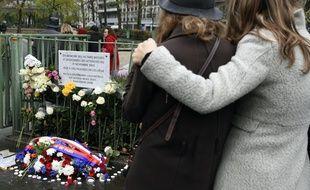 Le 13 novembre 2016, deux jeunes femmes se recueillent devant la plaque commémorative apposée rue de la Fontaine au Roi, près du café la Bonne Bière, touché par les attentats du 13-Novembre.