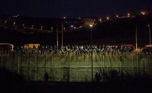 La garde civile espagnole surveille des immigrants venus d'Afrique perchés au sommet des barrières frontalières de Melilla le 13 août 2014