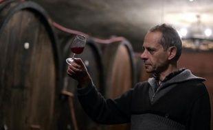 Le vigneron français Jean-Pierre Frick pose un verre de pinot noir à la main dans sa cave de Pfaffenheim, dans le Haut-Rhin, le 12 octobre 2015
