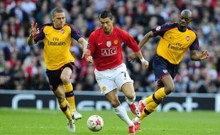 Cristiano Ronaldo (en rouge) au milieu de Gibbs et Diaby, lors de Manchester UNited Arsenal en Ligue des champions, le 28 avril 2009.