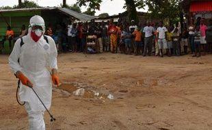 Un agent santiaire, en combinaison de protection, procède à une opération de désinfection dans un quartier de Monrovia où une personne est décédée du virus Ebola, le 10 septembre 2014 au Liberia