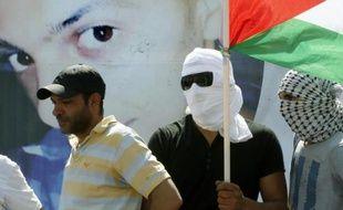 Un homme porte le drapeau palestinien derrière une photo géante de Mohammed Abu Khdeir, lors des funérailles de ce jeune palestinien, le 4 juillet 2014 à Jérusalem