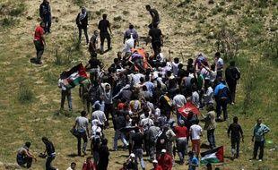Des Palestiniens portent un manifestant blessé à la frontière israélo-syrienne, sur les hauteurs du Golan (dimanche 5 juin 2011)