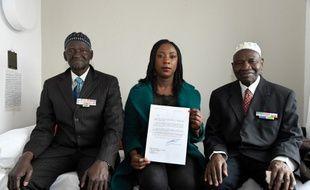Ousmane Sagna (G) et Guorgui M' Bodji (D), deux anciens tirailleurs sénégalais, posent aux côtés d'Aïssata Seck (C), qui tient une lettre de François Hollande, le 22 décembre 2016, à Bondy, près de Paris.