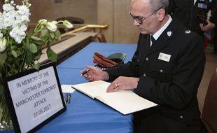 Un homme écrit dans un livre de condoléances de la ville de Peterborough, mis à disposition après l'attaque d'hier soir à Manchester