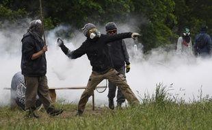 Un zadiste renvoyant une cartouche de gaz lacrymogène en direction des forces de l'ordre à Notre-Dame-des-Landes le 17 mai 2018.