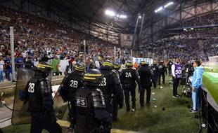 Des CRS arrivent sur la pelouse du Vélodrome pour calmer les supporters marseillais lors de OM-Lyon, le 20 septembre 2015.