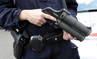 Un policier tient un flash-ball