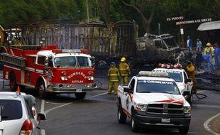 Des pompiers mexicains à côté d'un camion incendié le 1er mai 2015 à Guadalajara par des groupes à l'origine d'une vague de violences dans l'Etat de Jalisco