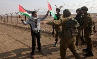 Des soldats israéliens empêchent un homme de mettre des drapeaux palestiniens sur le grillage marquant la frontière entre Israël et la Jordanie, le 1er janvier 2014