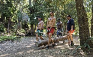Des candidats de «The Bridge» transportent un tronc d'arbre qui sera utilisé pour construire un pont.