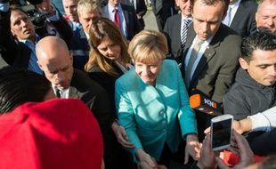 Angela Merkel serre la main de réfugiés alors qu'elle visite un centre d'enregistrement de demandes d'asile, le 10 septembre 2015 à Berlin