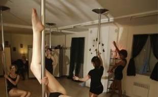 La pole dance consiste à enchaîner les figures acrobatiques autour de la barre.