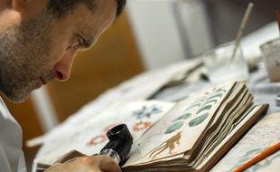 Un employé des éditions Siloe travaille à reproduire pour la première fois le manuscrit Voynich, le 9 août 2016 à Burgos, dans le nord de l'Espagne.
