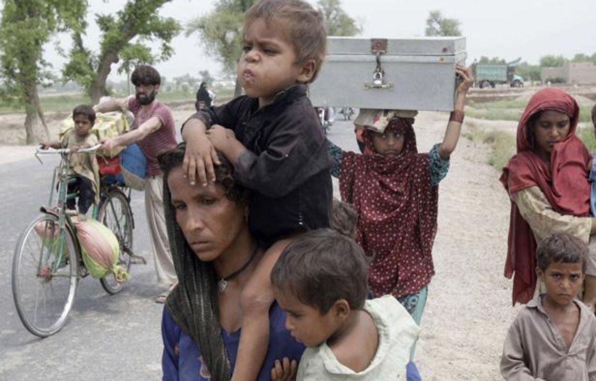 Des familles pakistanaises fuient leurs maisons après les inondations en août 2010. – K.M.Chaudary/AP/SIPA