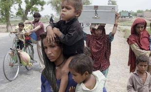Des familles pakistanaises fuient leurs maisons après les inondations en août 2010.