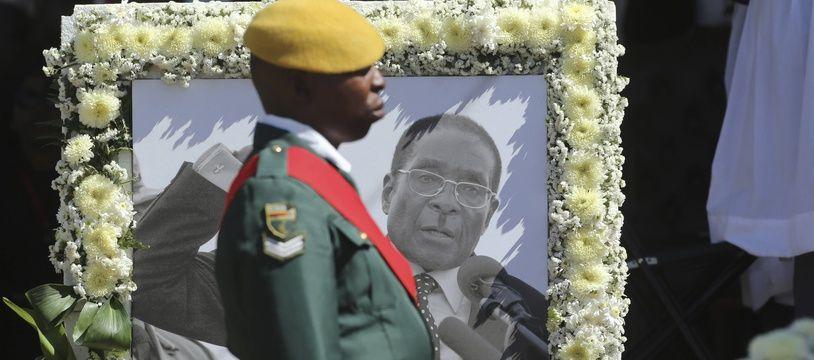 Un soldat devant un portrait de Robert Mugabe, lors des funérailles de l'ancien président à Kutama le 28 septembre 2019.