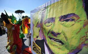 """Des partisans du """"Oui"""" au référendum sur la politique nucléaire, la privatisation de l'eau et l'immunité judiciaire du Premier ministre brandissent une affiche parodiant Silvio Berlusconi, le président duConseil le 13 juin 2011."""