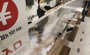 Une employée vérifie le film en plastique tendu devant les caisses comme rempart au coronavirus dans un magasin de Kitakyushu (sud du Japon), le 15 mai 2020.
