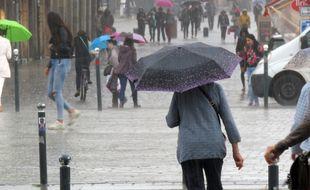 Illustration d'une personne marchant sous la pluie lors d'un orage en 218 à Rennes.
