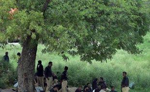 Des policiers pakistanais se reposent à l'ombre d'un arbre à Islamabad le 13 août 2014, où la situaiton est tendue à la veille de manifestations de l'opposition