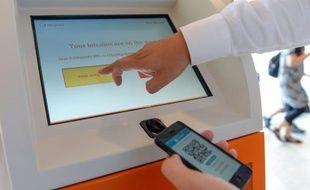 Une personne touche l'écran d'un distributeur de Bitcoin d'une entreprise espagnole à Barcelone le 10 juillet 2015