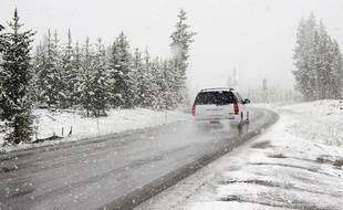 Une voiture en circulation sur une route de montagne légèrement enneigée.