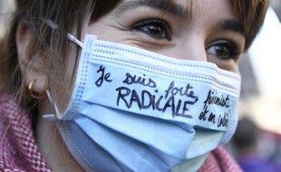 """""""Je suis forte, féministe, radicale et en colère"""", dit sur son masque cette femme dans une manifestation à Paris le 6 mars."""