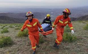 Des secouristes apportent du matériel pour venir en aide aux participants d'une course autour de Baiyin, en Chine le 22 mai 2021.