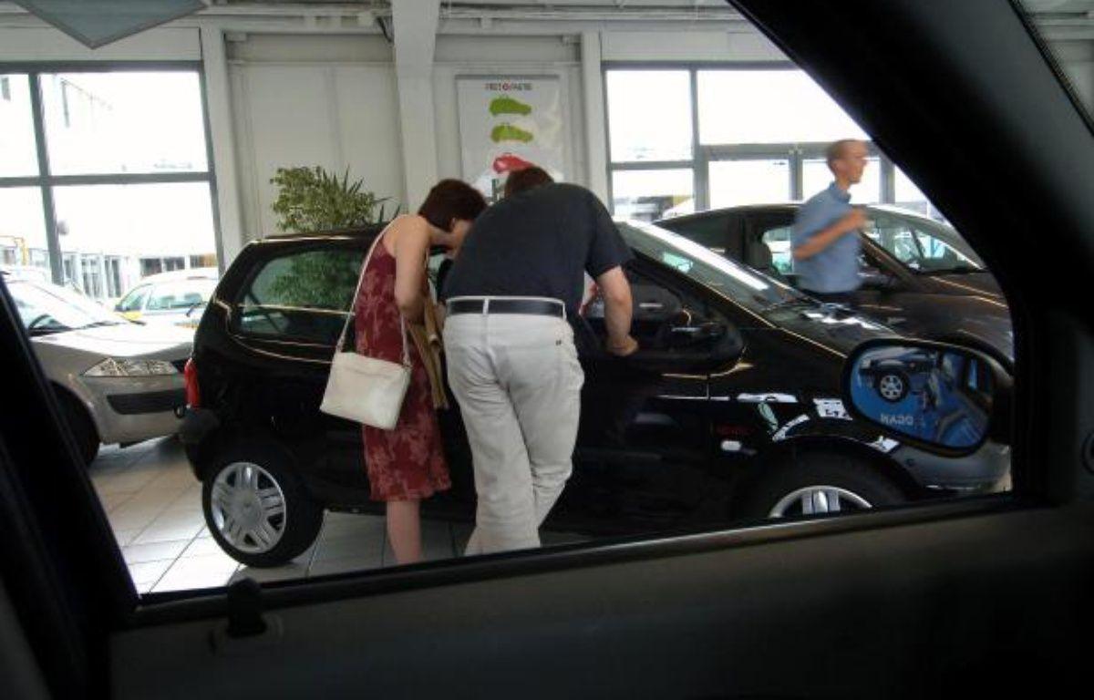 Un couple regarde l'intérieur d'une automobile chez un concessionnaire Renault. – MYCHELE DANIAU / AFP