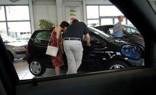 Un couple regarde l'intérieur d'une automobile chez un concessionnaire Renault.