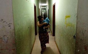 """Une femme Rom, son enfant dans les bras, dans un couloir du camp """"Best House"""", le 10 novembre 2014 à Rome"""