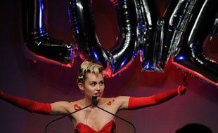 Miley Cyrus brandissant le mot LOVE (amour), lors du gala de l'AMFAR en juin 2015