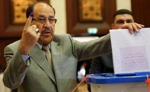 L'ex-Premier ministre Nouri al-Maliki montre son doigt taché d'encre après avoir voté aux élections parlementaires à Bagdad, le 30 avril 2014