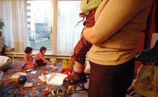 Une assistante maternelle gardant des enfants à domicile (illustration)
