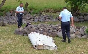 Des gendarmes près d'un débris d'avion retrouvé à la Réunion, le 29 juillet 2015.
