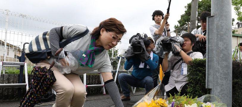 Une femme dépose des fleurs en hommage aux victimes de l'incendie de Kyoto Animation, le 19 juillet 2019.