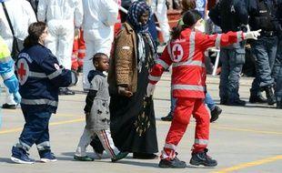 Des membres de la Croix Touge escortent des migrants qui arrivent dans le port de Messine, en Sicile, le 15 avril 2015