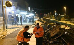 Des agents SNCF et la police près de voitures calcinées sur les voies ferrées devant la gare de Moirans, le 20 octobre 2015