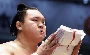 Le champion mongol de sumo Hakuho reçoit une liasse d'enveloppes contenant de l'argent des sponsors après avoir remporté un combat à Nagoya, le 23 juillet 2017.