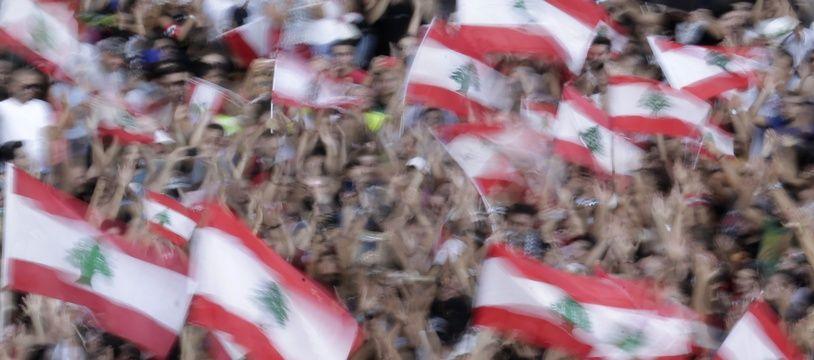 Des manifestants anti-gouvernement agitent des drapeaux du Liban, à Beyrouth, le 19 octobre 2019.