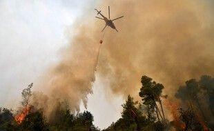 Un hélicoptère verse de l'eau sur un incendie de forêt le 5 août 2021, près du village de Kechries dans le nord d'Eubée, en Grèce.